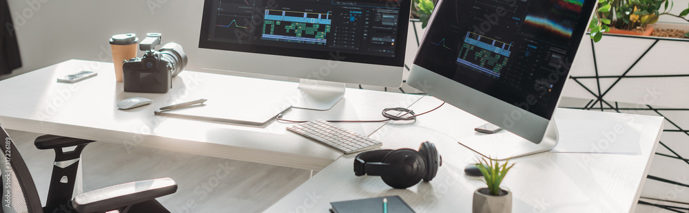 Fototapeta panoramic shot of computer monitors with storyboard near digital camera on table