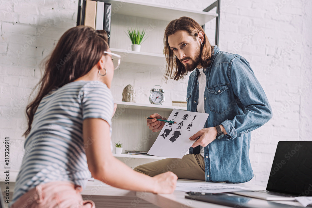 Fototapeta selective focus of bearded illustrator looking at woman and holding cartoon sketches
