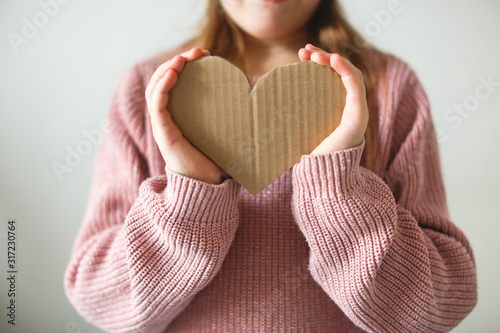 child with cardboard heart in her hands, charity