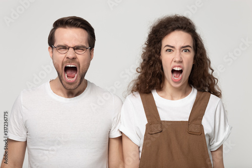 Valokuvatapetti Aggressive young man and angry millennial woman shouting, screaming together