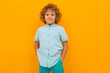 Leinwanddruck Bild - Little boy with curly hair in blue shirt and shorts