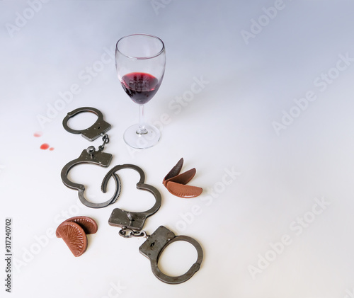 A drunken party, handcuffs on a cut-out background, chocolate, a glass of wine, drops of wine Canvas-taulu