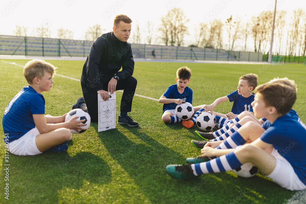 Fototapeta Group of Young Boys Sitting on Sports Grass Field witch School Coach. Kids Listening Coach's Tactic Talk. Young Coach Explain Football Tactic. Coaching Youths in Sports