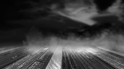 Dramatic black and white background. Cloudy night sky, moonlight, reflection on the pavement. Smoke and fog on a dark street at night.