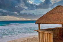 A Bamboo And Thatched Straw Hut Providing Shelter From A Stormy Sea And Sky