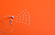 Leinwanddruck Bild - white earphones and white paper notes on orange background. view from above.