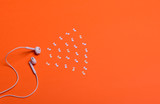 white earphones and white paper notes on orange background. view from above.