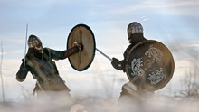Two Warriors Viking Are Fighting With Axes And Shields On The Winter Meadow.