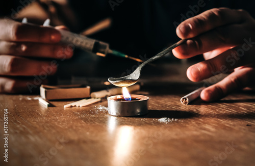 Man preparing heroin on fire Slika na platnu