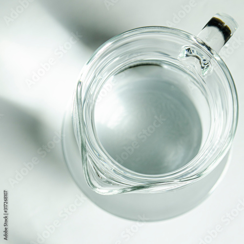 Fototapeta Pure clear water in a glass glass and glass jug stands on a white background obraz