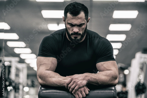 Obraz mental mind sport motivation concept of young handsome strong man with beard wearing black jersey concentration relaxation in sport gym - fototapety do salonu