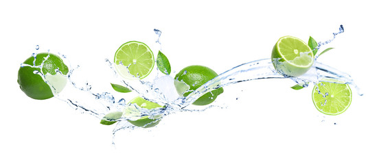 Ripe limes, fresh mint and splashing water on white background