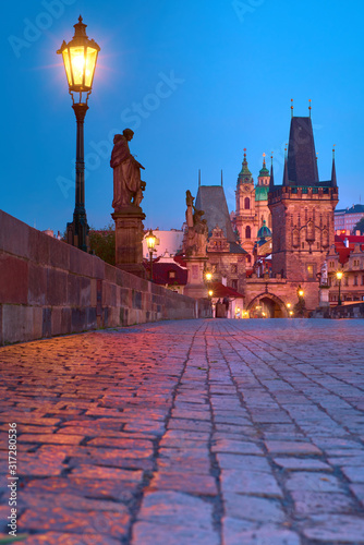 Charles Bridge at night with silhouette of a Saint, street light, historic buildings of Mala Strana, Lesser Bridge Tower and towers of Church of St. Nicolas Church and bellfry at dawn