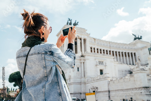 Young alone caucasian female tourist taking a photo of Victor Emmanuel II Monument using a modern smartphone on Piazza Venezia in Rome, Italy Fotobehang
