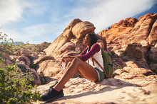Female Hiker Sitting On Edge O...