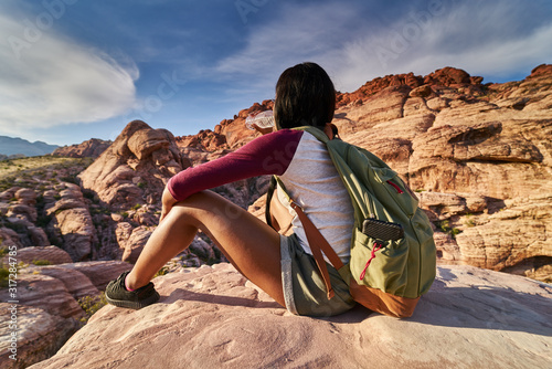 Obraz woman drinking from water bottle on top of boulder at red rock canyon park - fototapety do salonu