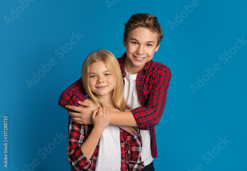 Happy siblings, brother and sister hugging and posing over blue background Tablou Canvas