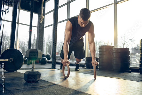 Obraz Flexible. Young muscular caucasian athlete training in gym, doing strength exercises, practicing, work on his upper body with rings rolling. Fitness, wellness, sport, healthy lifestyle concept. - fototapety do salonu