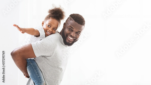 Black cheerful daddy holding his little daughter on his back