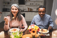 Selective Focus Of Smiling Multicultural Man And Woman Talking And Eating Pasta During Dinner