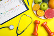 Leinwanddruck Bild - Fruits, dumbbells, stethoscope and list of products on yellow background, flat lay. Visiting nutritionist