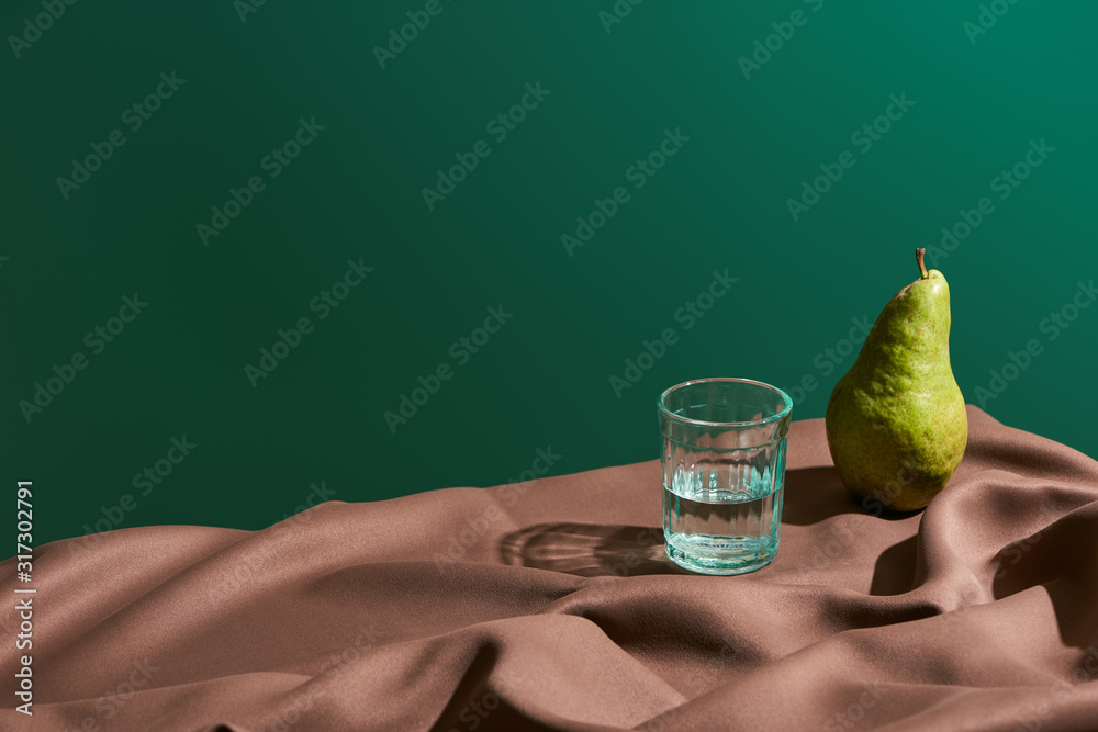Obraz classic still life with pear and water in glass on table with brown tablecloth isolated on green fototapeta, plakat