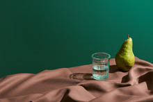 Classic Still Life With Pear And Water In Glass On Table With Brown Tablecloth Isolated On Green