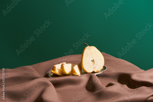 Fotografía classic still life with cut pear on silver plate on table with brown tablecloth