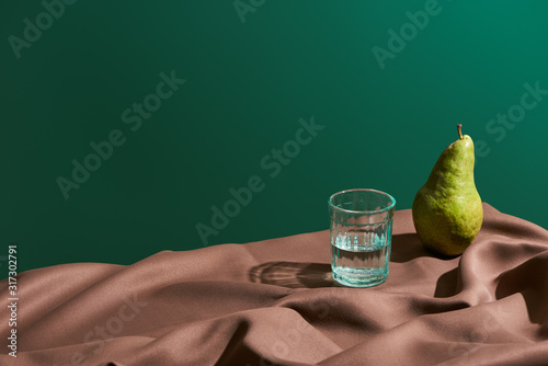 Fototapeta classic still life with pear and water in glass on table with brown tablecloth isolated on green obraz
