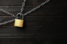Steel Padlock, Chains And Space For Text On Black Wooden Background, Flat Lay. Safety Concept