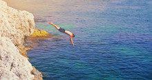 Young Man Jumping Off Cliff In...