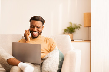 Guy Working On Laptop Chatting On Phone Sitting At Home