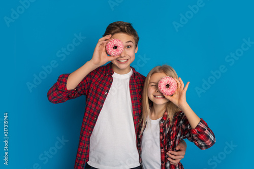 Fototapeta Happy siblings covering eyes with donuts, posing together over blue background