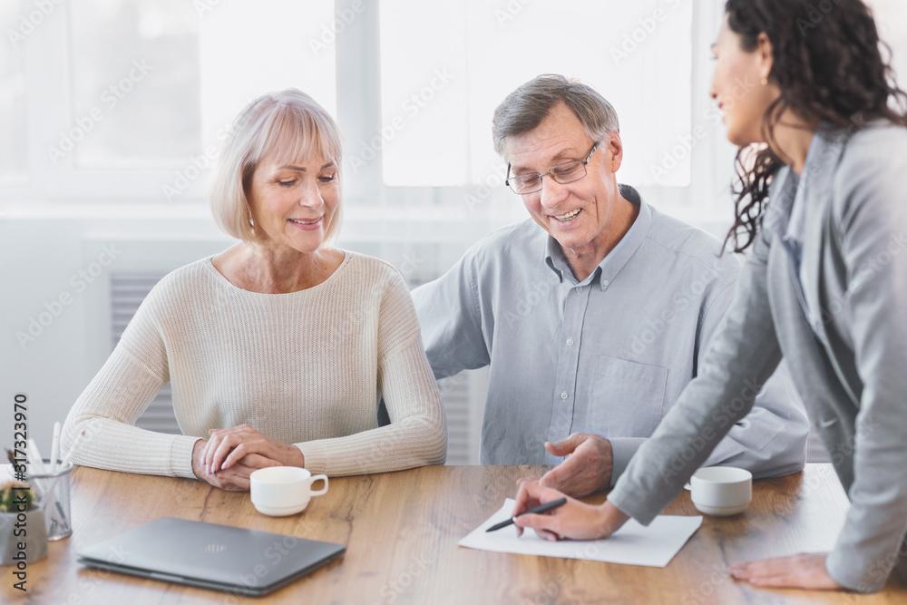 Fototapeta Mature couple talking to financial advisor at office