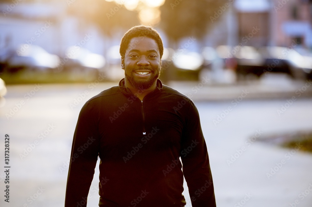 Fototapeta Portrait of a smiling African-American man in a park under sunlight with a blurry background
