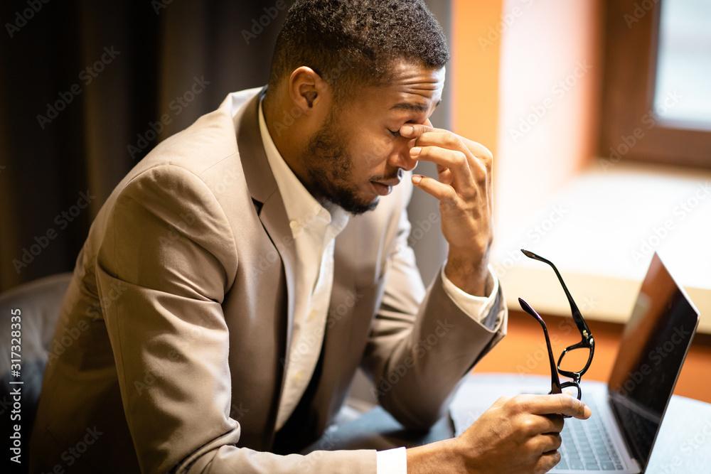 Fototapeta Exhausted black manager massaging nose while using laptop