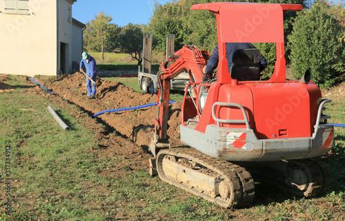Fototapeta Pose des tuyaux dans la tranchée de raccordement d'une maison. obraz