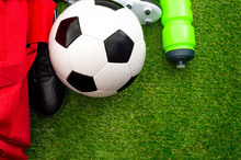 Sport Competition, Wellness Through Exercising And Athletics Concept With Leather Soccer Ball, Red Sports Training Bag, Football Boots Or Cleats, Bottle Of Water On Green Grass Or Pitch Background