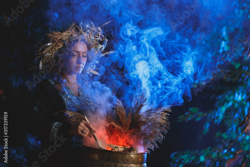 Fotografía A forest witch brews a potion holding a Voodoo doll.