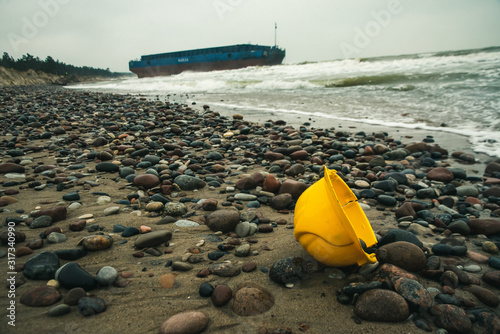 a yellow safety head helmet washed ashore during a storm and a ship washed ashor Canvas Print