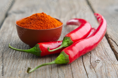 Whole and ground to powder red chili pepper on wooden kitchen table Fototapete