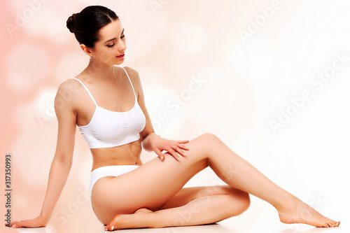 Fotografia Pretty woman with slim beautiful body touching her smooth skin sitting against a