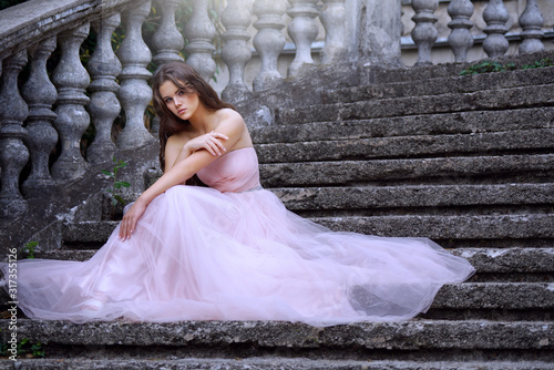 young caucasian girl woman in pink fashion dress outdoors  sunlight nature castle #317355126
