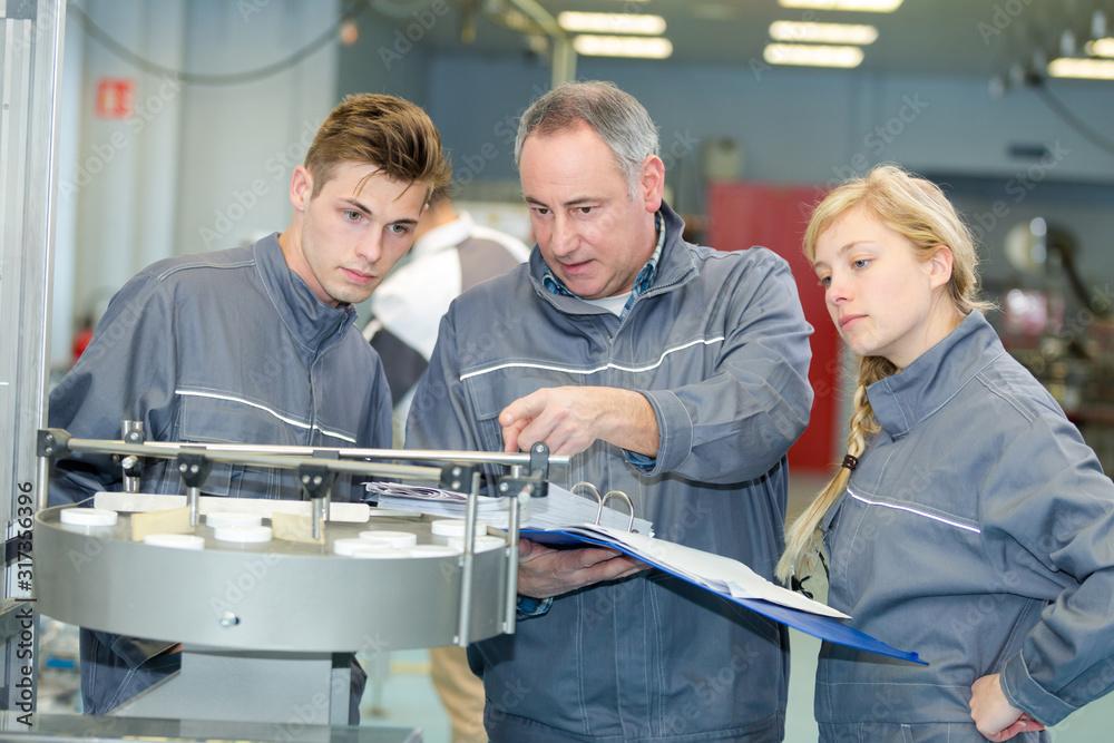 Fototapeta metal worker showing machine room to apprentice