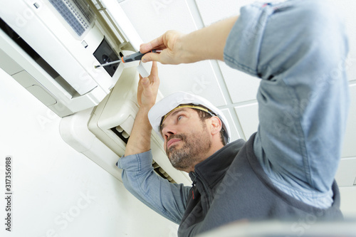 Fotomural young man cleaning air conditioning system