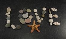 Word LOVE Made Of Sea Smooth Stones And Seashells On Black Granite With White Spots Background With Starfish