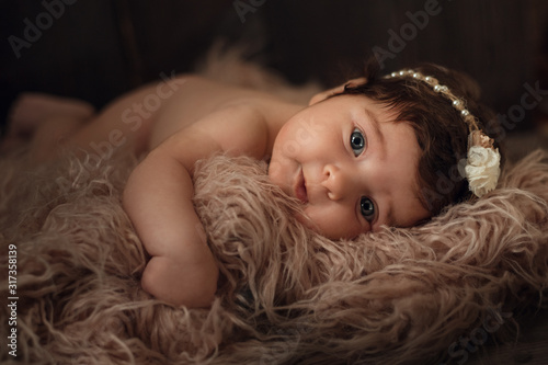 Newborn baby, beautiful infant lies in pink fur blanket on wood background Canvas Print