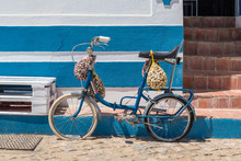 Bicycle Caring Snails In Meshes In Front Of A Blue And White House In Algarve, Portugal