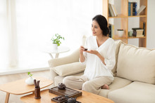 Mature Woman Drinking Tea In Living Room