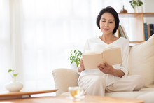 Mature Woman Reading Book On S...